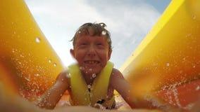 видео 4K: Скольжения мальчика голодают раздувным сползают в водный бассейн с активной камерой перед его стороной сток-видео