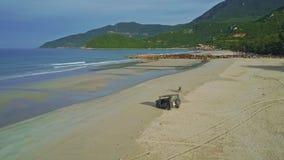 Виллис вида с воздуха воинский на влажном пляже океана песка сток-видео
