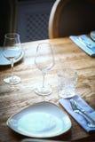 Вилка и нож на таблице, около плиты Стоковые Изображения