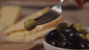 Вилка принимает оливку от плиты, следующей на таблице сыр акции видеоматериалы