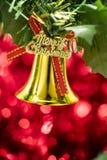 Вид орнамента колокола рождества на ветви дерева с красным backg bokeh Стоковые Изображения