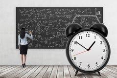 Вид сзади дамы дела которая пишет формулы математики на черной доске Огромный будильник на переднем плане Conc стоковые изображения rf