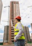 Вид сзади архитектора указывая с светокопиями на unde здания стоковая фотография rf