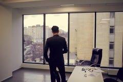 Вид сзади бизнесмена в офисе смотря вне окно на n Стоковое Изображение