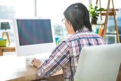 Вид сзади бизнесмена используя компьютер Стоковое Фото