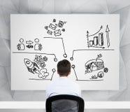 Вид сзади бизнесмена на рабочем месте которое смотрит диаграммы, долевую диограмму, значки дела которые нарисованы на whitebo Стоковое Изображение RF