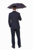 Вид сзади бизнесмена под зонтиком Стоковое Фото