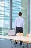 Вид сзади бизнесмена стоя в офисе с руками в карманн Стоковое Фото
