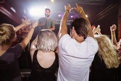 Вид сзади вентиляторов наслаждаясь с оружиями подняло на nighclub Стоковые Фото