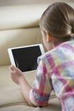 Вид сзади девушки используя ПК таблетки дома Стоковая Фотография