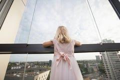 Вид сзади девушки смотря через окно Стоковая Фотография RF