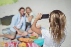Вид сзади девушки фотографируя ее родителей на пляже Стоковые Фотографии RF