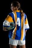 Вид сзади женского игрока рэгби держа шарик Стоковое Фото