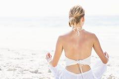 Вид сзади женщины выполняя йогу на пляже Стоковое Фото