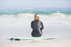 Вид сзади женщины в мокрой одежде сидя с surfboard на пляже Стоковое Изображение RF