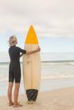 Вид сзади женщины держа surfboard пока стоящ на береге Стоковые Фотографии RF