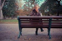Вид сзади женщины на скамейке в парке Стоковая Фотография RF