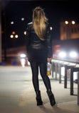 Вид сзади женщины представляя на шоссе на ноче стоковые фото