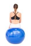 Вид сзади женщины пригонки сидя на шарике тренировки Стоковое фото RF