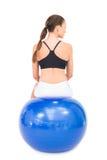 Вид сзади женщины пригонки сидя на шарике тренировки Стоковые Изображения RF