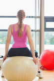 Вид сзади женщины пригонки сидя на шарике тренировки Стоковые Фото