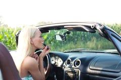 Вид сзади женщины прикладывая губную помаду в автомобиле с откидным верхом Стоковые Изображения RF