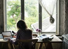 Вид сзади женщины работая на компьтер-книжке компьютера на деревянном столе Стоковые Фото