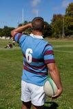 Вид сзади игрока держа шарик рэгби на игровой площадке Стоковое Фото
