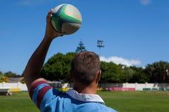 Вид сзади игрока рэгби держа шарик на игровой площадке Стоковая Фотография