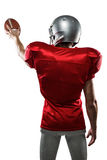 Вид сзади игрока спорта в красном jersey держа шарик Стоковые Изображения