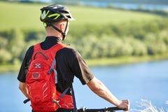 Вид сзади и конец-вверх велосипедиста стоя с горным велосипедом против реки Стоковые Изображения RF