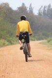 Вид сзади катания человека велосипеда на грязной улице с питьевой водой Стоковое Изображение RF