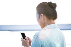 Вид сзади коммерсантки используя ее smartphone Стоковые Фотографии RF