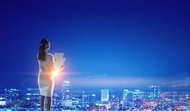 Вид сзади коммерсантки смотря город ночи Мультимедиа Стоковое Изображение RF