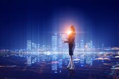 Вид сзади коммерсантки смотря город ночи Мультимедиа Стоковые Изображения RF
