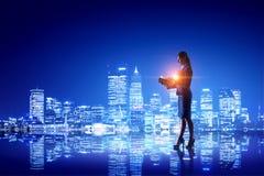 Вид сзади коммерсантки смотря город ночи Мультимедиа Стоковые Фото
