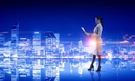 Вид сзади коммерсантки смотря город ночи Мультимедиа Стоковое Изображение