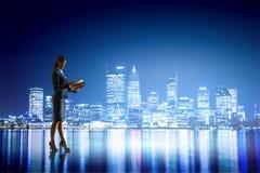 Вид сзади коммерсантки смотря город ночи Мультимедиа Стоковая Фотография