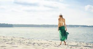 Вид сзади красивой женщины в зеленом шелке идя вдоль моря Стоковое Изображение RF