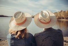 Вид сзади крупного плана человека и женщины сидя на пляже и уборной Стоковое Изображение