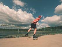 Вид сзади к встроенному конькобежцу в красной футболке и черных брюках катаясь на коньках на мосте Внешний встроенный кататься на Стоковые Изображения RF