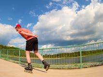 Вид сзади к встроенному конькобежцу в красной футболке и черных брюках катаясь на коньках на мосте Внешний встроенный кататься на Стоковое Фото