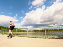 Вид сзади к встроенному конькобежцу в красной футболке и черных брюках катаясь на коньках на мосте Внешний встроенный кататься на Стоковые Фото