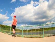 Вид сзади к встроенному конькобежцу в красной футболке и черных брюках катаясь на коньках на мосте Внешний встроенный кататься на Стоковая Фотография RF
