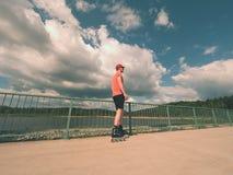 Вид сзади к встроенному конькобежцу в красной футболке и черных брюках катаясь на коньках на мосте Внешний встроенный кататься на Стоковые Изображения