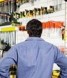 Вид сзади клиента стоя в магазине оборудования Стоковые Изображения