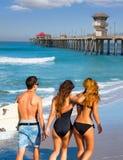 Вид сзади мальчиков и девушек серферов идя на пляже стоковое фото