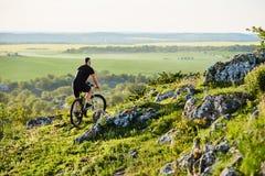 Вид сзади молодого велосипедиста ехать велосипед на скалистом следе в лете Стоковые Изображения RF