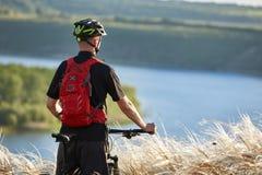 Вид сзади молодого велосипедиста стоя с горным велосипедом против красивого реки Стоковые Изображения RF