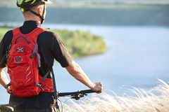 Вид сзади молодого велосипедиста стоя с горным велосипедом против красивого реки Стоковые Фото